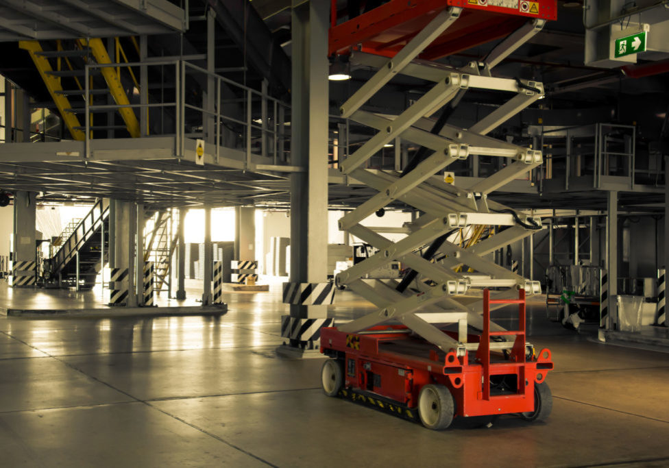 49070159 - distribution warehouse hall with hydraulic scissors lift platform, vintage color style
