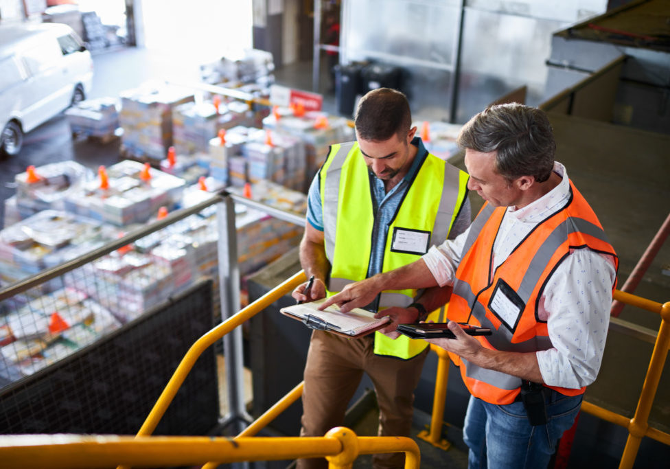 Shot of two warehouse workers standing on stairs using a digital tablet and looking at paperwork